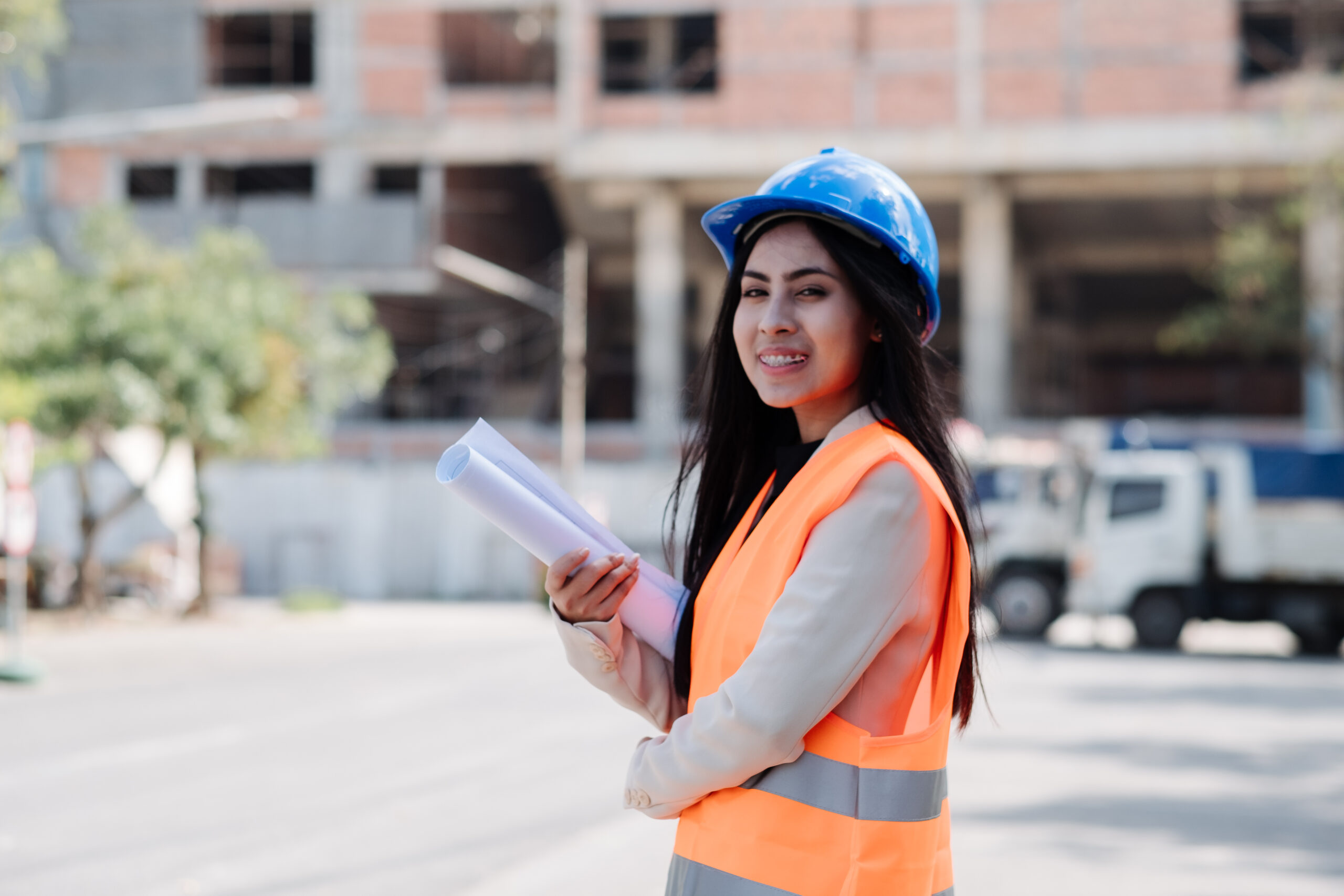 Asian woman engineer with the blue safety helmet meeting at the construction site with blueprints and laptop.